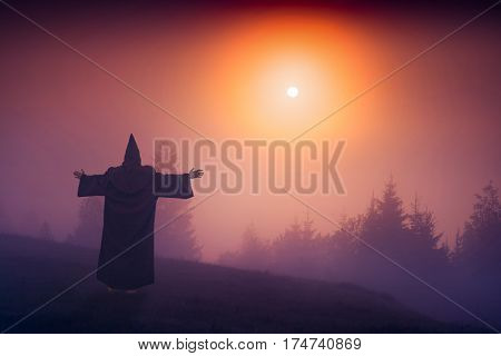 Fairy wizard in a black cassock standing on a hill and welcome raising sun above the foggy valley.