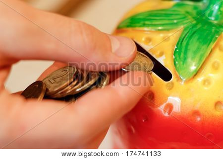 The Hand Throws The Coin In The Moneybox In The Form Of Strawberries. Person Saving Money; Currency