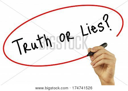 Man Hand Writing Truth Or Lies? With Black Marker On Visual Screen. Isolated On Background. Business