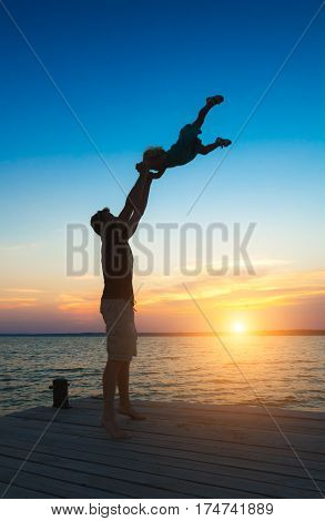 Father and daughter playing on the pier at the sunset time. Concept of friendly family.