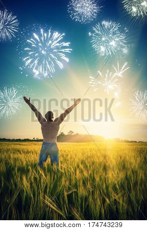 Man who enjoy holiday firework in a wheat field at sunset light