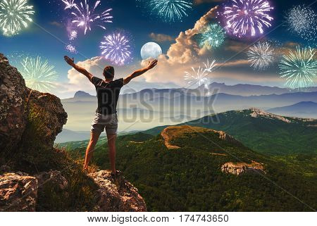 Men standing on a cliff with rised hands and enjoy the holiday firework in a mountain valley