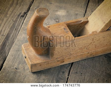 Old used wood plane on a rustic workbench vintage color style