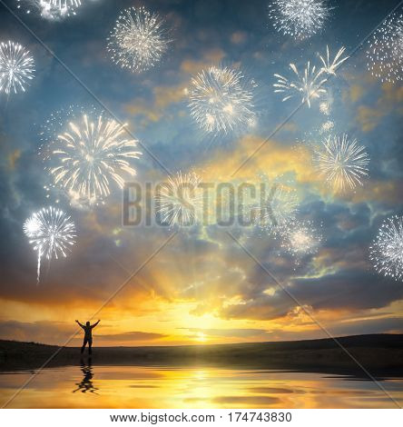 Men who welcome firework on sunrset with raised hands on a sea coast