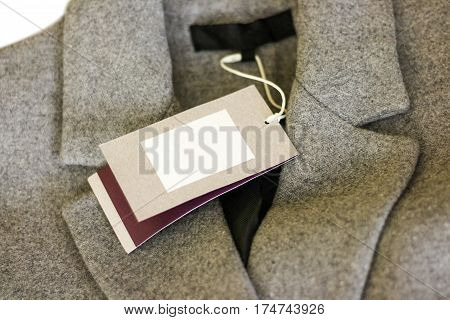 Close Up Price Tag Of Grey Wool Coat. Clothes, Wear And Fashion Concept.