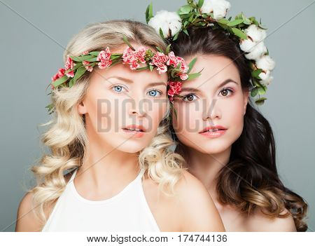 Two Beautiful Women with Long Curly Hair Perfect Skin and Summer Flowers. Beauty Cosmetology and Aesthetic Medicine