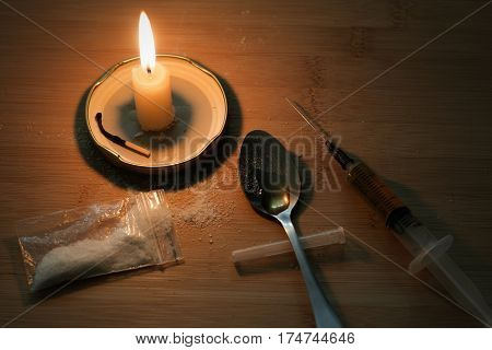 Drug Syringe And Cooked Heroin On Spoon. Cocaine In The Bag, Scattered. Candle Burns. Evening.