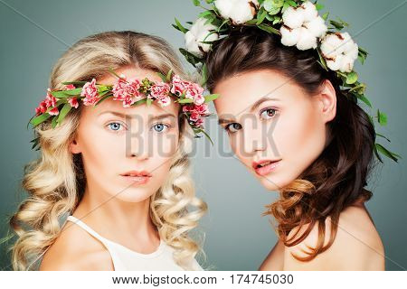 Two Perfect Women Fashion Model with Long Curly Hair and Summer Flowers Wreath. Beauty Cosmetology and Aesthetic Medicine Concept