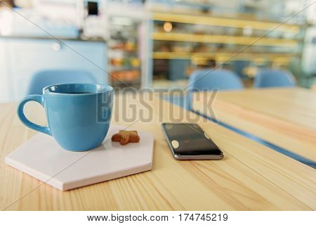 Close up of blue small utensil with bracing nonalcoholic drink is on white stand near small star cookie. Mobile phone beside delicious composition