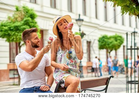 A beautiful young couple are siting on a bench and eating ice-cream on the street of Budapest, Hungary.