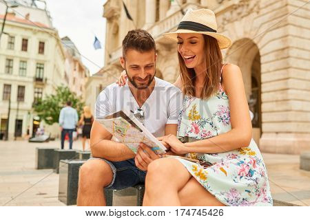 A beautiful young couple are sitting and holding a map and looking around at the Egyetem Square in Budapest, Hungary.