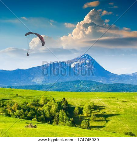 Paraglide silhouette flying over Carpathian spring mountain valley. Majestic landscape with beautiful red clouds above the high mountains