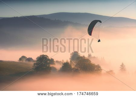 Paraglide silhouette in a light of sunrise above the misty carpathian valley.