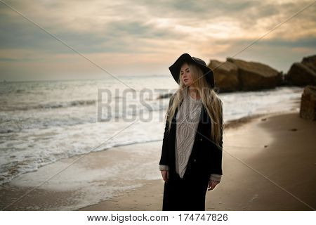 Woman In Hat And Coat On Winter Beach At Sunset.