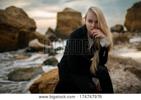Woman In Sweater And Coat Sitting On Rock On Winter Beach At Sun