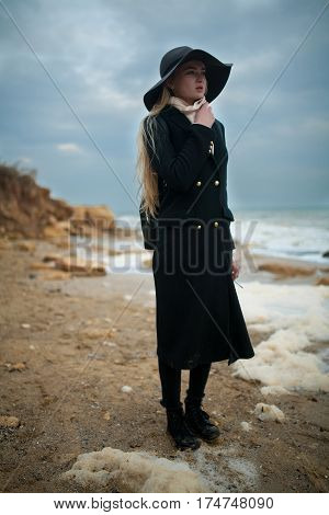 Woman In Hat And Coat On Winter Beach Among Sea Foam.