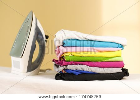 Iron Stands With Stacks Of Ironed Colored Linen. Pile Of Clothes. Ironing Concept. All Colors Of The