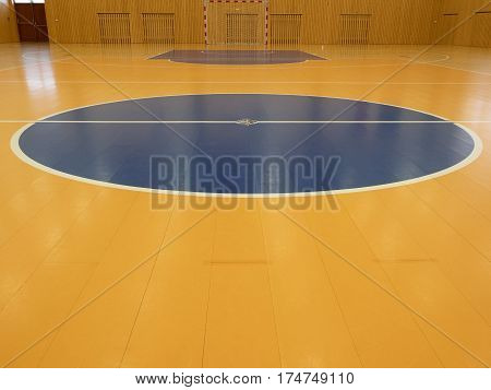 Basketball court inside. White lines and blue playfield in hall. Hanball gate at wall. Painted wooden floor of sports hall with colorful marking lines. Schooll gym hall
