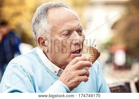 Senior man enjoying city and eating icecream.