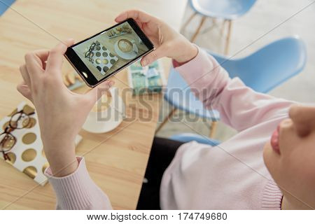 Girl is sitting at table. She making photo of cup with coffee and eyewear on notebook. Top view. Focus on screen