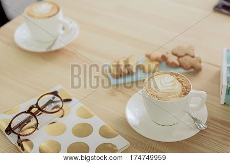 Two small cups of bracing drink with crema beside close bright notebook and eyeglasses. Close up