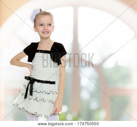 Beautiful little girl in fancy white dress with a black belt against a huge arched Windows.