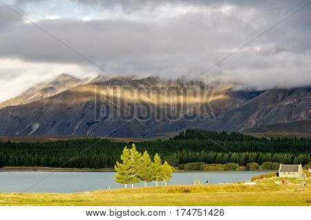 Sun breaking through the clouds over Lake Tekapo and the Church of the Good Sheppard on the South Island of New Zealand