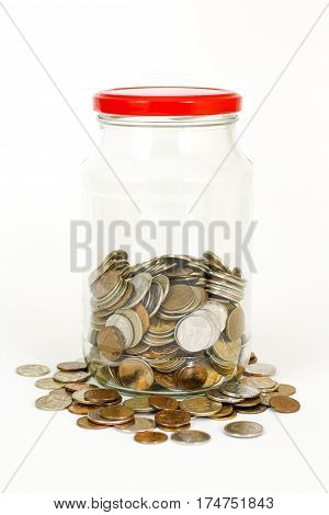 Close Up Coins In Glass Jar On White Table. Coins Scattered Around. Isolated On White Background.