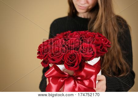 Girl In Black Jacket Holding In Hand Rich Gift Bouquet Of 21 Red Roses. Composition Of Flowers In A