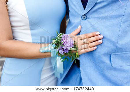 Young woman with a floral boutonniere on a hand in a blue dress hugging a man in a blue suit