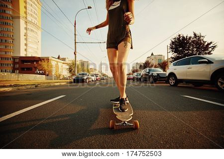 Beautiful young girl with tattoos riding on his longboard on the road in the city in sunny weather. Extreme sports. Rear view of motion