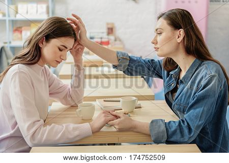 Two serious girls are sitting near table. They holding hands. Lady patting on head her upset girlfriend with sympathy