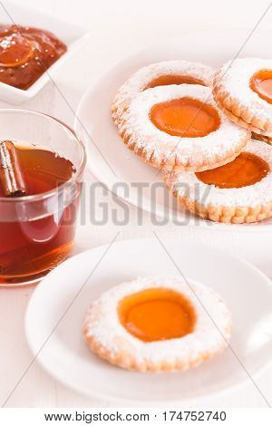 Teatime biscuits  with jam on wooden table.