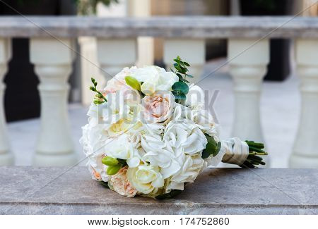 Beautiful wedding bouquet of roses and eustoma on a vintage marble banister