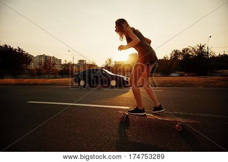 Beautiful young girl with tattoos riding on her longboard on the road in the city in sunny weather. Extreme sports