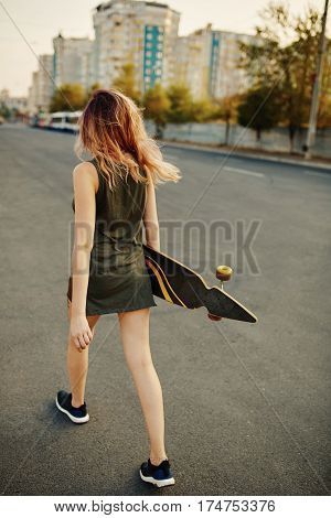 Beautiful young tattooed woman with her longboard on the road in the city in sunny weather