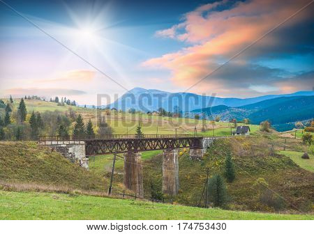 Sunrise above the Carpathian mountain valley with old railway bridge through the river