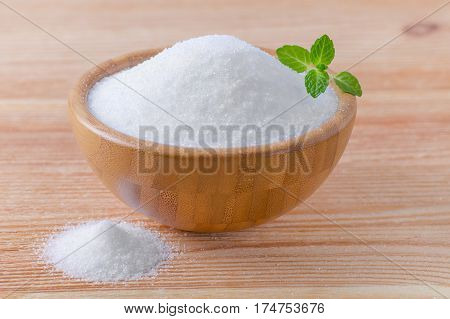 birch sugar xylitol in a wood bowl with mint on wooden background