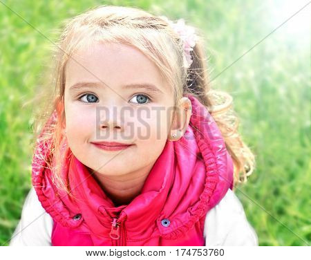 Portrait of adorable little girl on the meadow outdoor