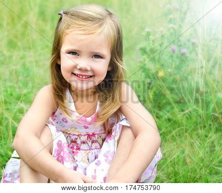 Cute little girl sitting in the grass on the meadow in summer day