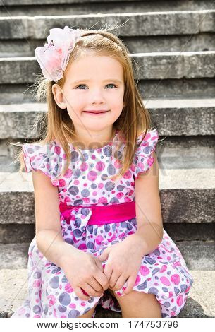 Portrait of adorable little girl in princess dress sitting on the speps