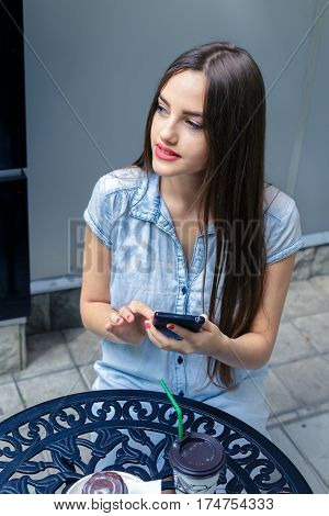 Beautiful young woman using phone in outdoors cafe at summer day.