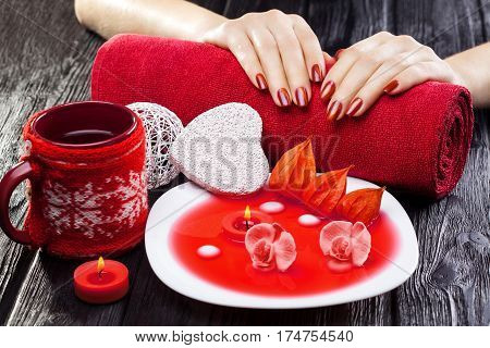 beautiful red manicure with oil and candles, red orchid flower and towel on the black wooden table.