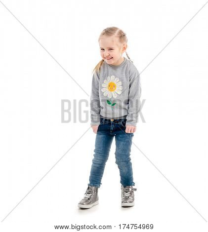 Little blonde child smiling awkwardly, wearing blue jeans and gray sweatshirt, isolated on white background