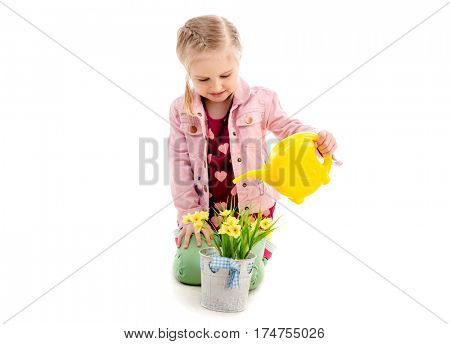 Adorable kid watering flowers with yellow watering can, wearing pink jacket, isolated on white background