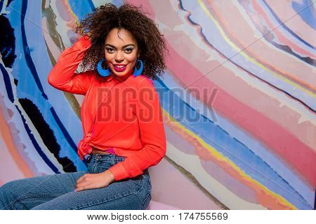 Beaming mulatto woman with bright makeup situating near colorful wallpaper. Copy space in right side