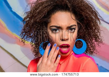 Portrait of Astonishing curly african female with blue faicepaint and nail varnish locating against variegating poster