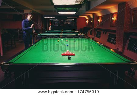 Playing pool, man aiming the billiard ball, snooker