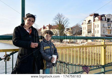 UZHGORODUKRAINE - MARCH 04 2017: Poor woman with little girl begging for alms in the street of Uzhhorod Ukraine.