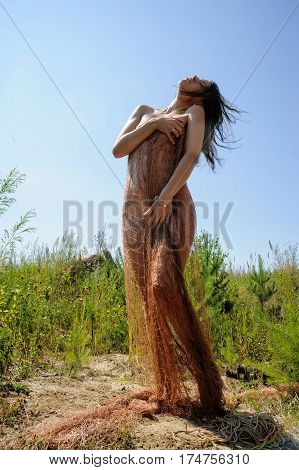 Pretty naked woman covering in fishnet at nature background